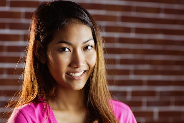 Femme asiatique souriante à la caméra sur le mur de briques