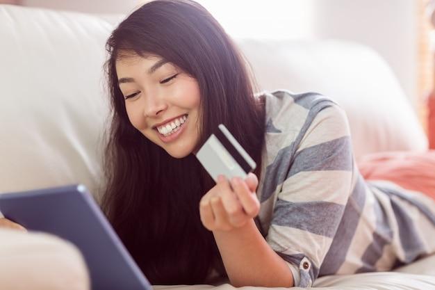 Femme asiatique souriante sur canapé avec tablette pour magasiner en ligne à la maison dans le salon