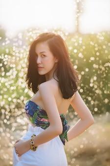 Femme asiatique souriante dans un parc et regardant la caméra