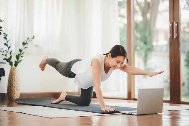 Femme asiatique souriante faisant un bras une planche de jambe pour exercer la classe d'entraînement en ligne de muscle de base