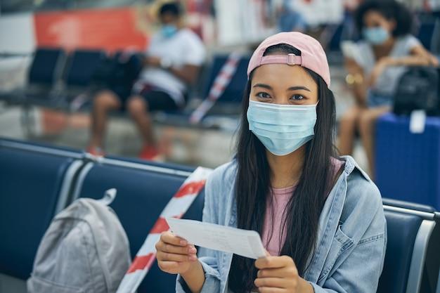 Femme asiatique souriante et heureuse tenant un billet tout en posant et en regardant l'appareil photo sur le banc de l'aéroport international
