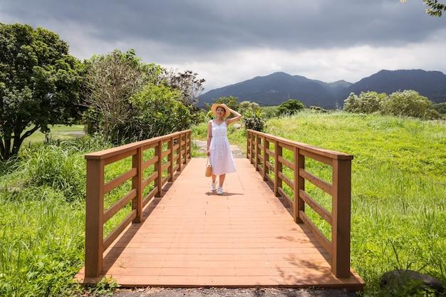 Femme asiatique souriante marchant dans la nature par temps nuageux