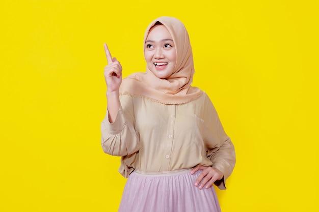 Femme asiatique souriante portant le hijab avec son doigt pointé isolé sur fond de bannière jaune clair
