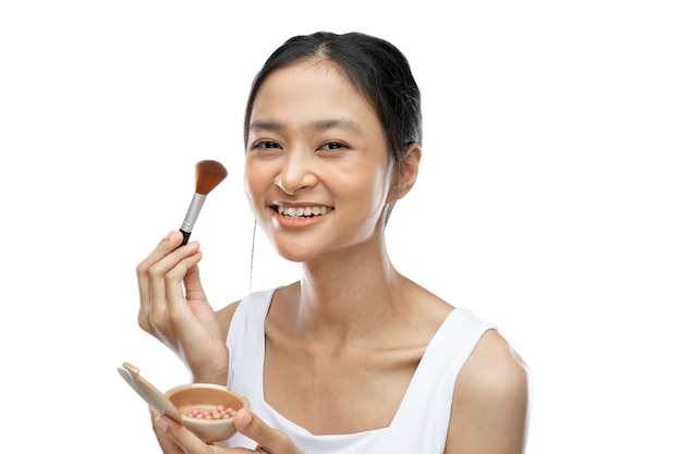 Femme asiatique souriante portant des sous-vêtements appliquant du maquillage avec un pinceau