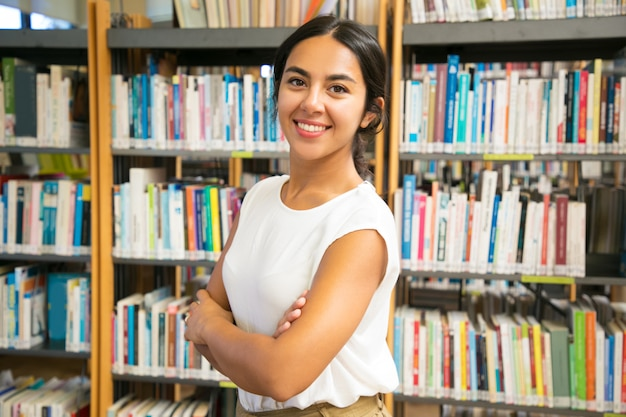 Femme asiatique souriante posant à la bibliothèque publique
