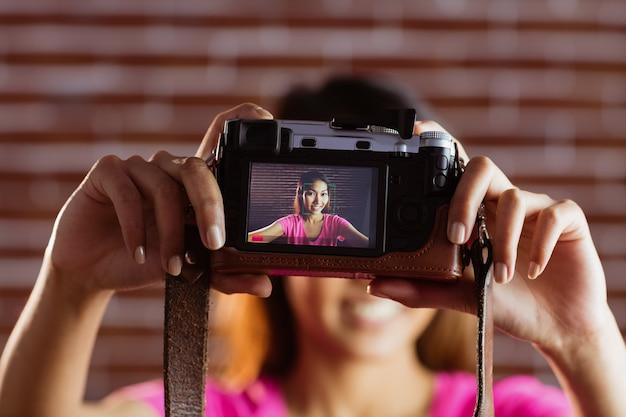 Femme asiatique souriante prenant une photo avec la caméra sur le mur de briques