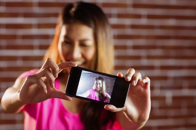 Femme asiatique souriante prenant selfie avec smartphone sur mur de briques