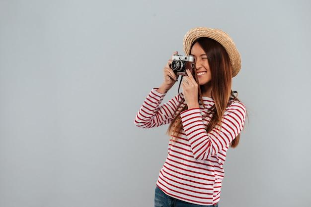 Femme asiatique souriante en pull et chapeau faisant photo