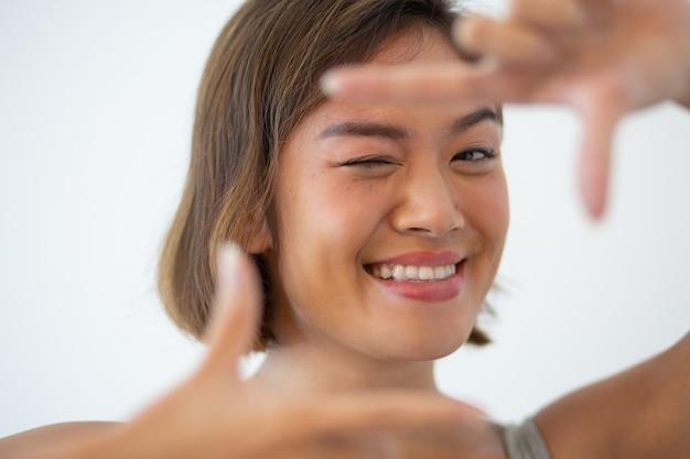 Femme asiatique souriante regardant la caméra et faisant un geste de la trame