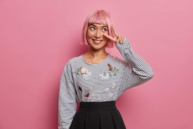 Une femme asiatique souriante satisfaite fait un geste de paix sur les yeux, montre deux doigts, regarde pensivement de côté, vêtue de vêtements élégants à la mode