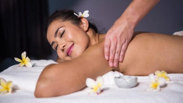 Femme asiatique souriante se détendre avec un massage à l'huile thaï sur le lit dans un salon spa. soin du corps
