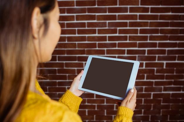 Femme asiatique souriante avec tablette sur le mur de briques