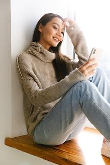 Femme asiatique souriante tapant sur son téléphone portable alors qu'elle était assise sur le rebord de la fenêtre à l'intérieur