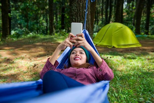 Femme asiatique souriante avec téléphone au repos dans un hamac