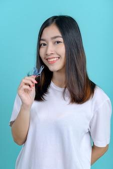 Femme asiatique souriante tenant un appareil de rétention orthodontique sur fond d'écran bleu. soins dentaires et dents saines.