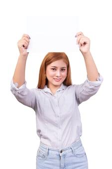 Femme asiatique souriante tenant une bannière blanche vierge, panneau de signalisation d'entreprise avec un tracé de détourage