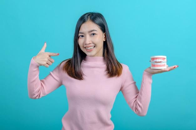 Femme asiatique souriante tenant un modèle de dent sur fond d'écran bleu. soins dentaires et dents saines.