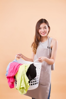 Femme asiatique souriante tenant un panier à linge
