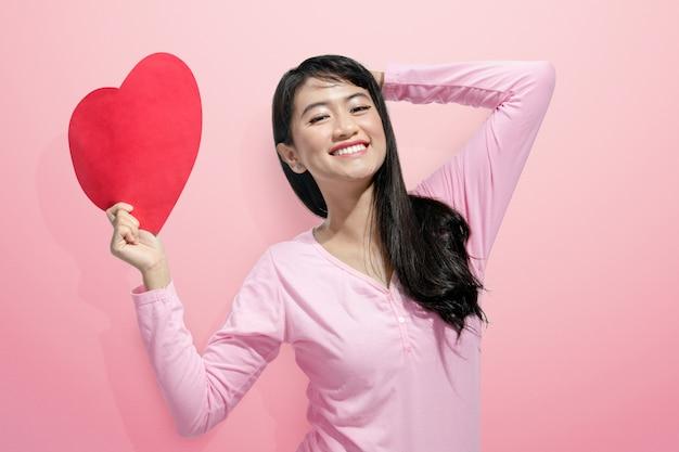 Femme asiatique souriante tenant un papier coeur rouge
