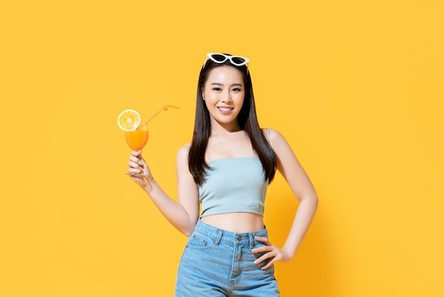 Femme asiatique souriante en tenue d'été avec un verre de jus d'orange