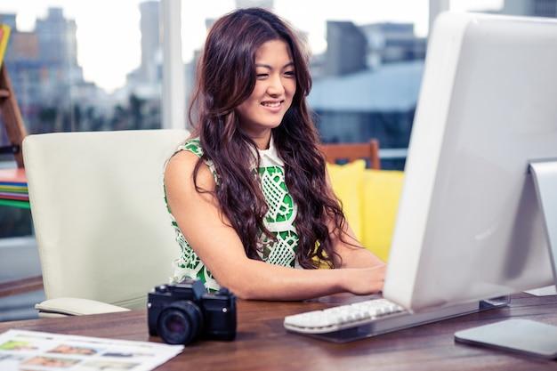 Femme asiatique souriante travaillant sur l'ordinateur de bureau
