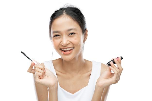 Femme asiatique souriante vêtue d'une sous-robe blanche tenant du mascara