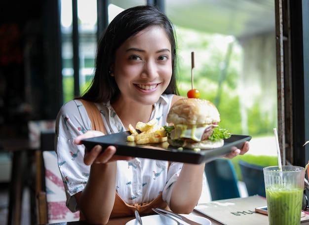 Femme asiatique, sourire, manger, hamburger, à, café