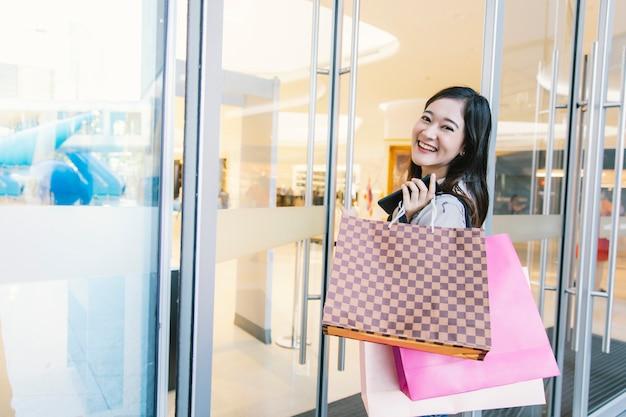 Femme asiatique sourire avec des sacs à provisions profiter dans un centre commercial