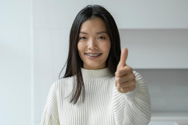 Une femme asiatique sourit et donne un coup de pouce à la caméra