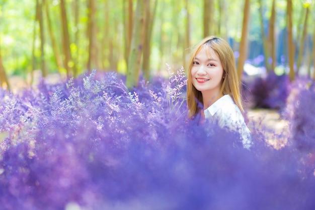 Une femme asiatique sourit joyeusement dans le jardin de fleurs violettes au premier plan sur un thème naturel.