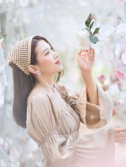 Une femme asiatique sourit et se tient dans un jardin de fleurs de roses blanches comme thème naturel et luxueux