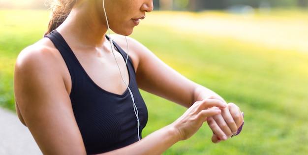Femme asiatique sport, écouter de la musique avec des écouteurs tout en regardant regarder en plein air