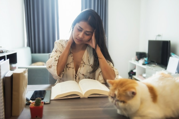 Une femme asiatique stressée lit un gros livre de texte et masse le cou et le cerveau dans le salon avec de jolis cheveux exotiques à poil court. douleur ou douleur due au travail acharné ou à la lecture. elle a la migraine.