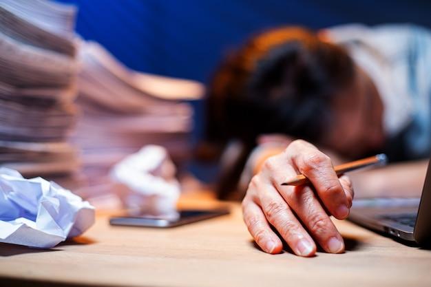 Femme asiatique surmenée et endormie sur la table après s'être sentie très éprouvante. dépression et anxiété. une fille de bureau chinoise qui dort après ne peut pas trouver de données et de solution pour faire son rapport. des bourreaux de travail.