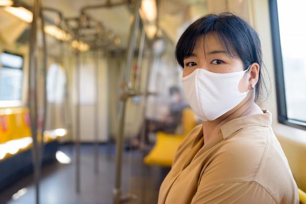 Femme asiatique en surpoids avec masque assis à distance à l'intérieur du train