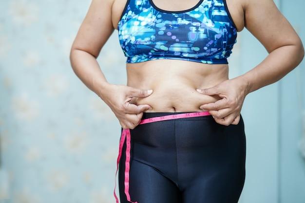 Femme asiatique en surpoids montre le gros ventre au bureau.