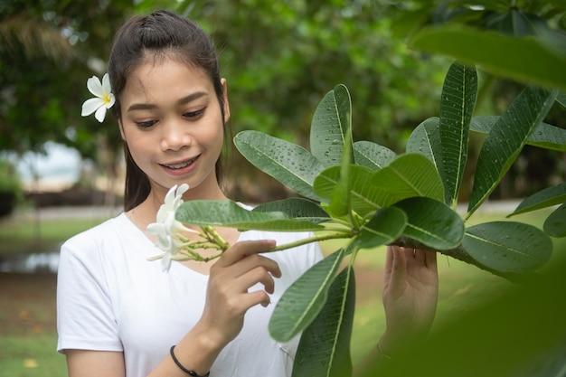 Femme asiatique, t-shirt blanc, plumeria, cheveux