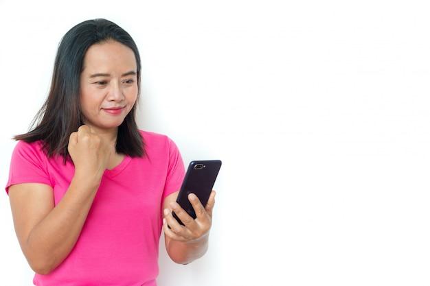 Femme asiatique en t-shirt avec smartphone sur fond blanc.