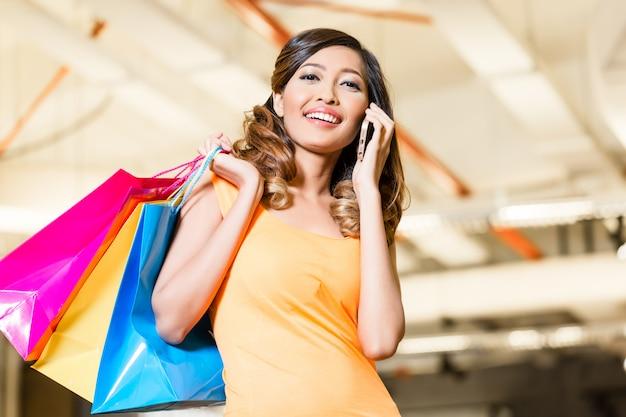 Femme asiatique avec téléphone achats mode