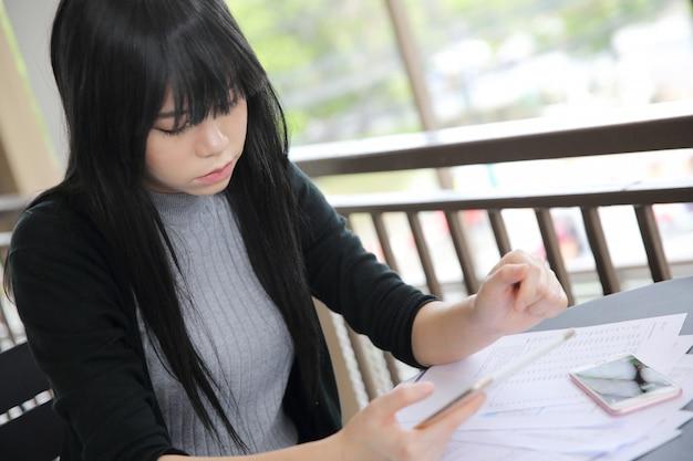 Femme asiatique avec un téléphone intelligent avec les entreprises