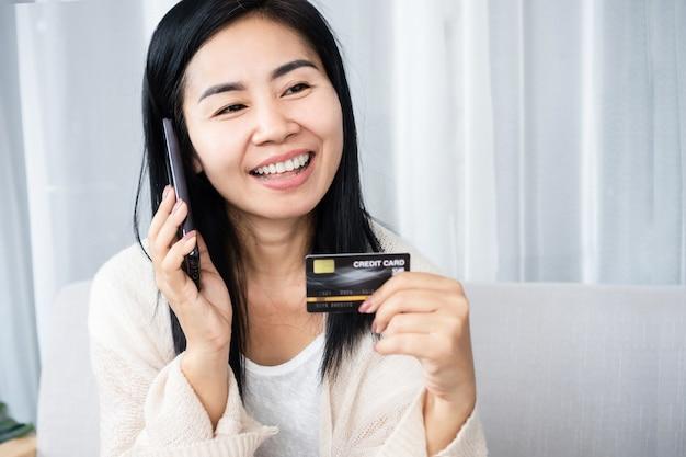 Femme asiatique avec téléphone portable appelant la banque pour un service de carte de crédit