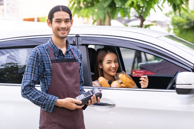 Femme asiatique tenant une carte de crédit et payer à partir de la voiture