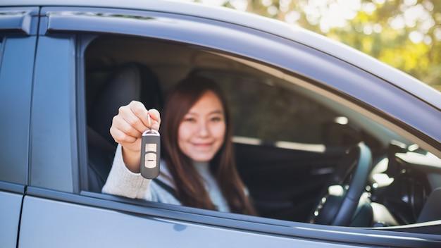Une femme asiatique tenant une clé de voiture alors qu'elle était assise dans la voiture