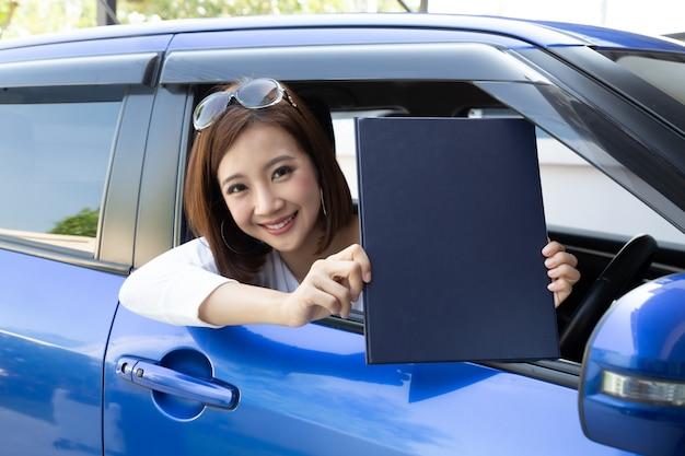 Femme asiatique tenant un document papier et assis dans la voiture.