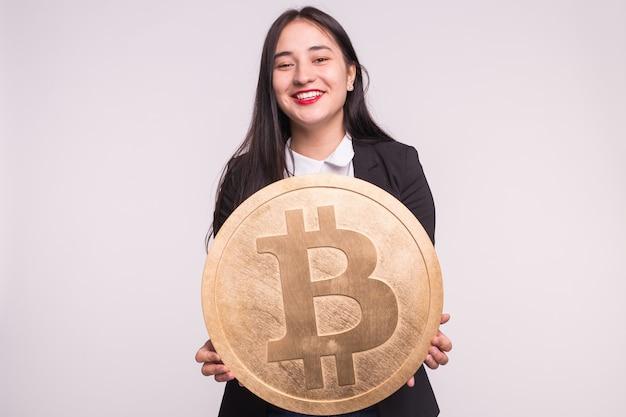 Femme asiatique tenant gros bitcoin sur mur blanc. concept d'investissement de crypto-monnaie.