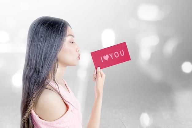 Femme asiatique tenant un papier rouge avec texte je t'aime avec fond clair flou. la saint-valentin