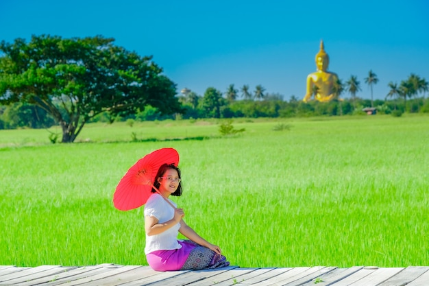 Une femme asiatique tenant un parapluie rouge assis sur un pont en bois dans une rizière avec une grande image de bouddha doré.