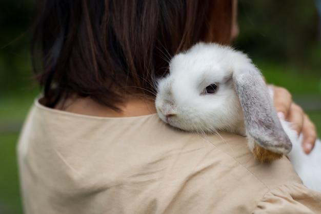 Femme asiatique tenant et portant un lapin mignon avec tendresse et amour. amitié avec le lapin de pâques mignon. lapin heureux avec le propriétaire.
