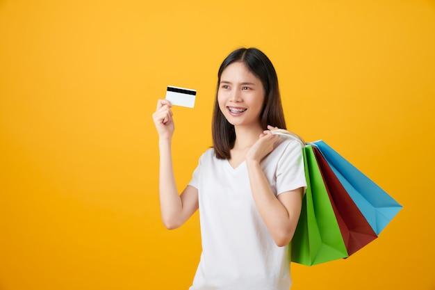 Femme asiatique tenant des sacs à provisions et une carte de crédit