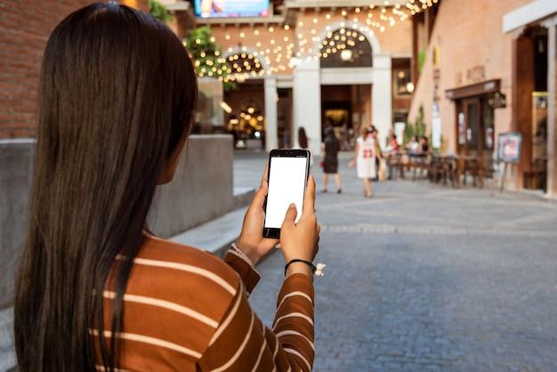 Femme asiatique tenant smartphone en marchant dans la rue.
